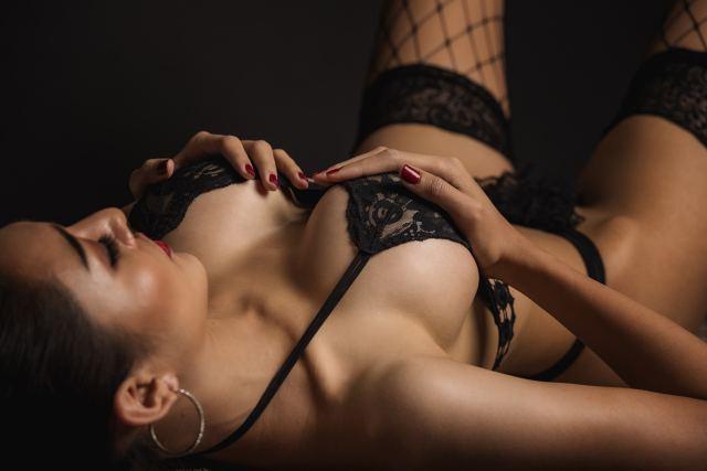schöne dunkelhaarige Frau posiert liegend in Reizwäsche