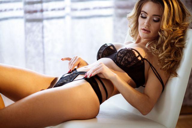 attraktive Frau posiert liegend in Reizwäsche